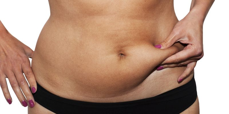 Woman's fingers  measuring  her belly fat